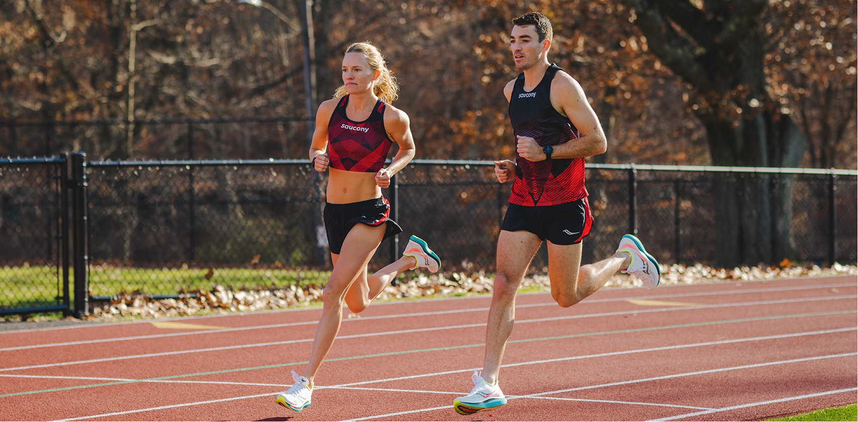 Man and woman running on a track with Saucony apparel and running shoes.