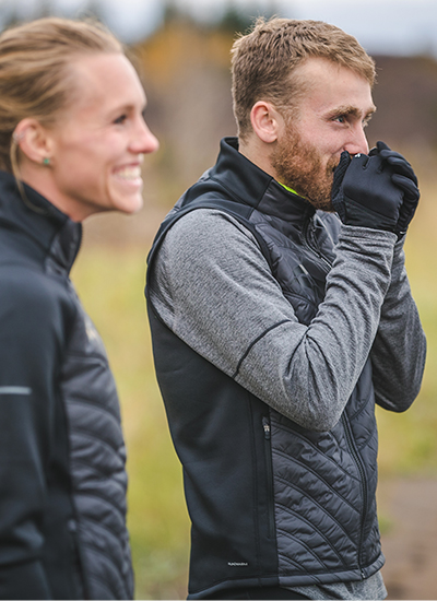 Woman and man getting ready to run in the winter wearing Saucony apparel