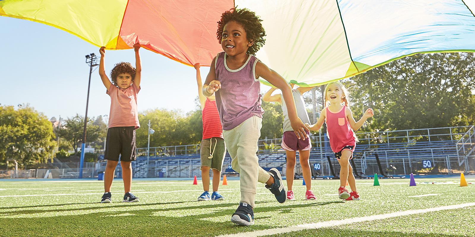 Kids playing under a rainbow parachute.