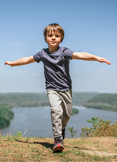 A kid at the top of a hill with a lake behind.