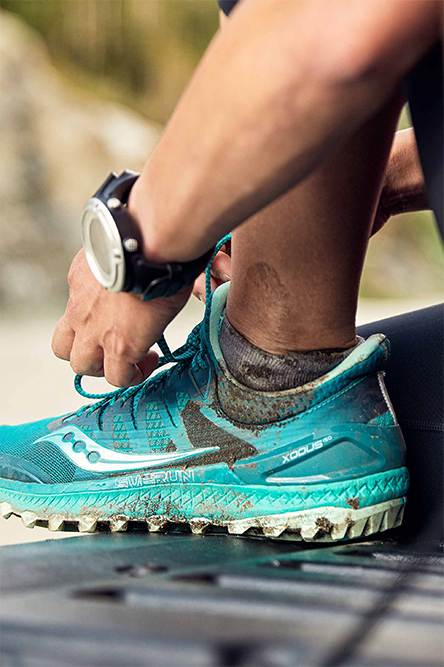 Closeup of a teal Xodus ISO 3, a little bit dirty. The wearer is tying their shoelaces.