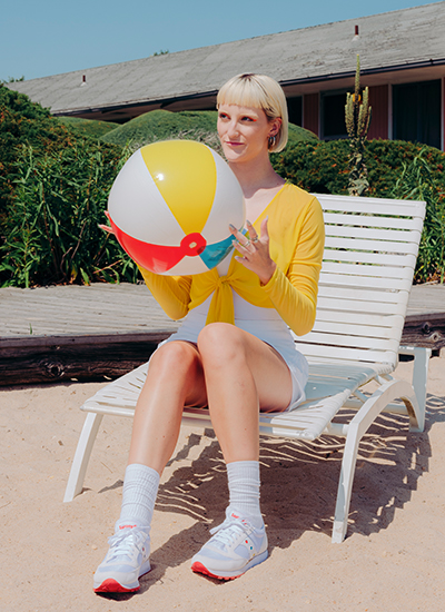 A person sitting in a pool chair and holding a beach ball while wearing shoes that match their outfit perfectly.