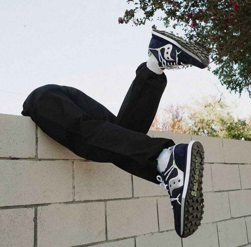A person climbing over a wall, wearing Saucony Originals.