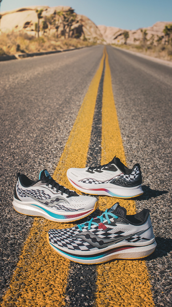 Three Endorphin shoes on the double-yellow line of a dead-straight desert road disappearing into distant mountains.