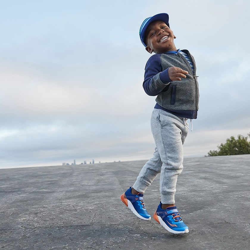 A little boy jumping and smiling.