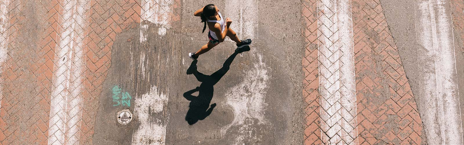 Top down view of a woman running on a brick and concrete road with white vertical lines.