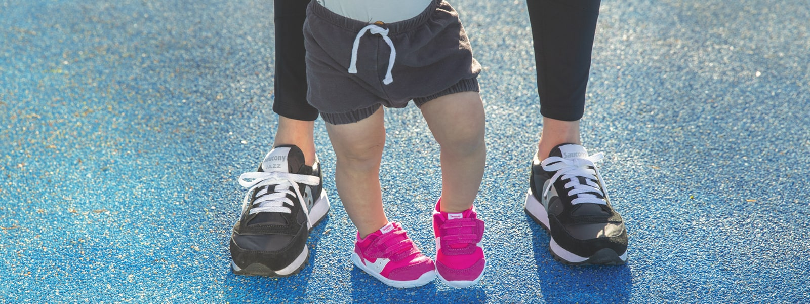 Close of a parents and kids feet, wearing Sauzony Jazz Shoes.