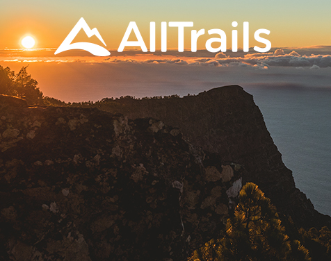 Trail near cliff overlooking clouds and sunset