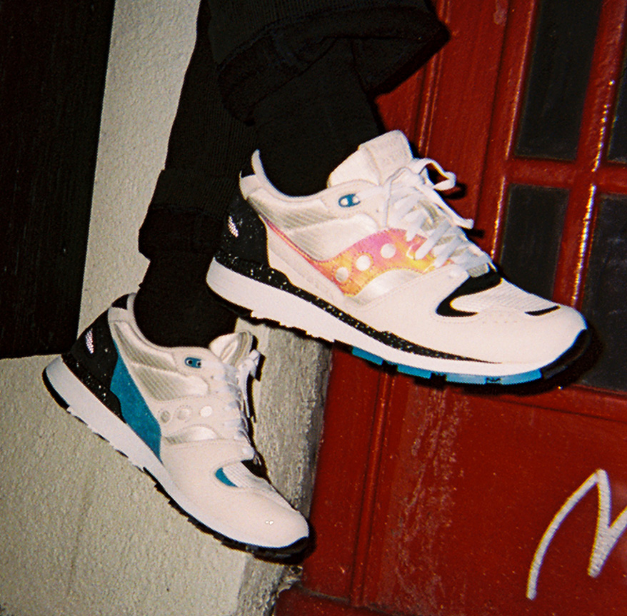 Close up of a pair of Saucony's on a person's feet.