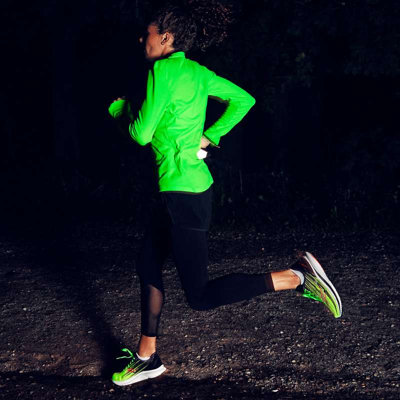 A women running in brightly reflective shirt and running shoes
