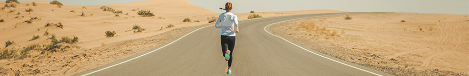 A lone runner jogs down the middle of a desert highway.