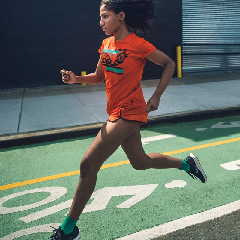 A woman running in bright orange gear and Saucony shoes.