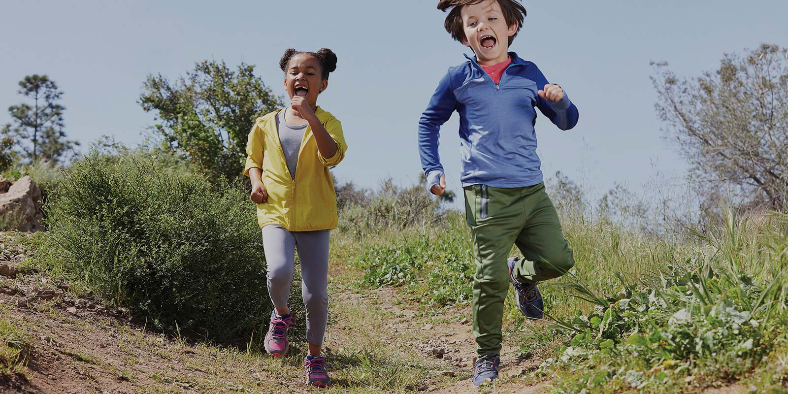 Children running down a hill with their mouths wide open having fun with trees and bushes in the background