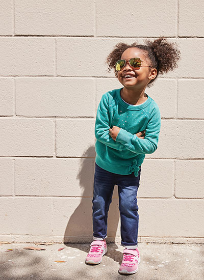 Girl wearing sunglasses and Saucony shoes