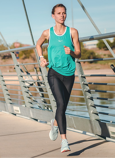 Woman running on a bridge with her Liberty ISO2 shoes.