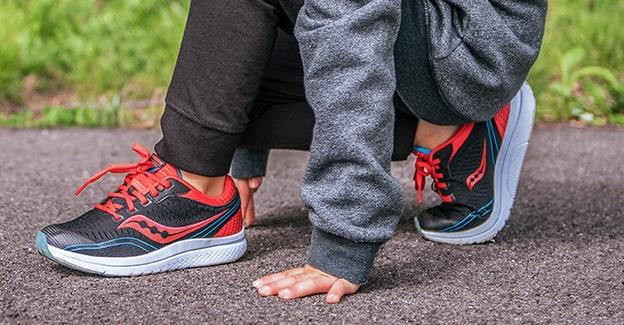 A kid kneeling, wearing Saucony running shoes.